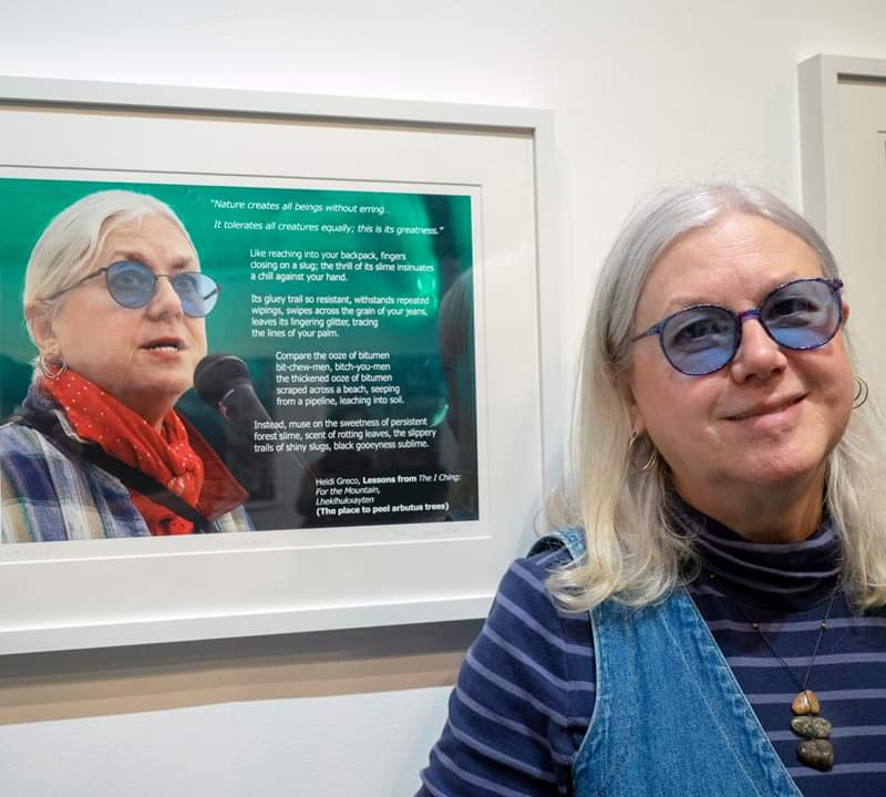 Poet and Environmentalist Heidi Greco stands with her portrait